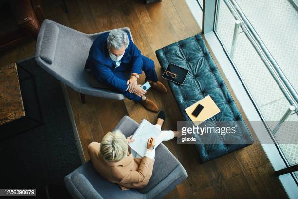 back at the office during coronavirus pandemic. - business meeting stock pictures, royalty-free photos & images