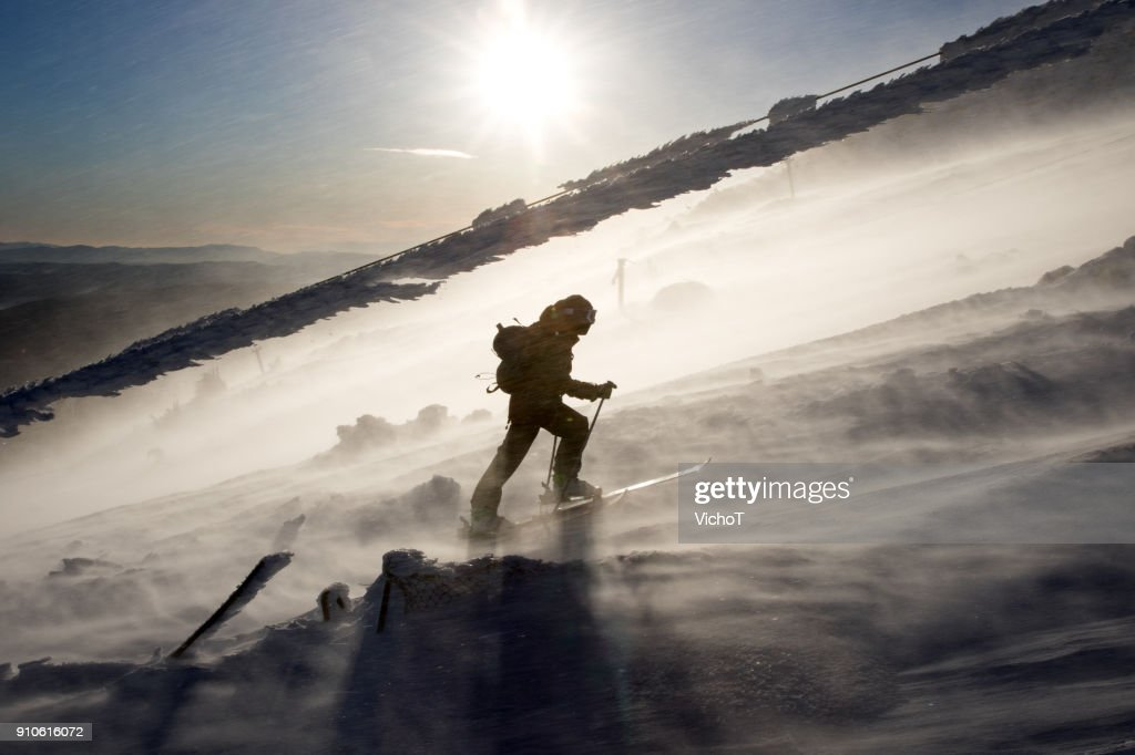 Back country skier climbing a mountain in a severe storm. : Stock Photo