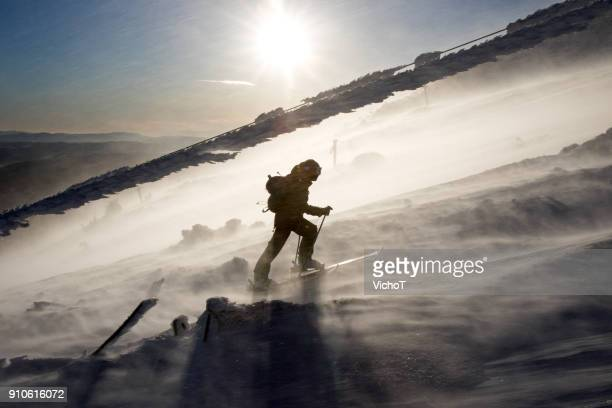 Back country skier climbing a mountain in a severe storm.