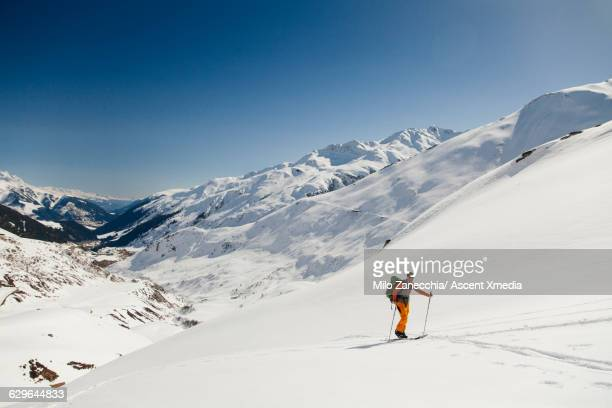 Back country skier pauses to admire scene ahead
