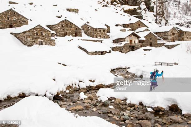 Esquiador parte país caminando hacia el antiguo pueblo de mountani