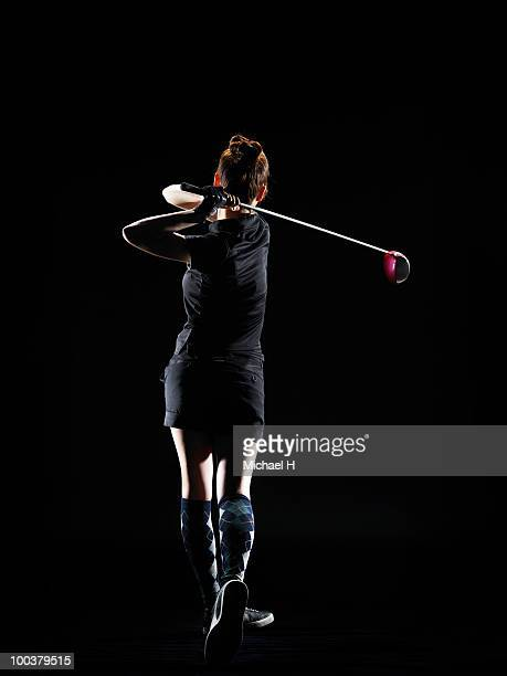 back figure of lady golfer who shook off driver - ゴルフのスウィング ストックフォトと画像