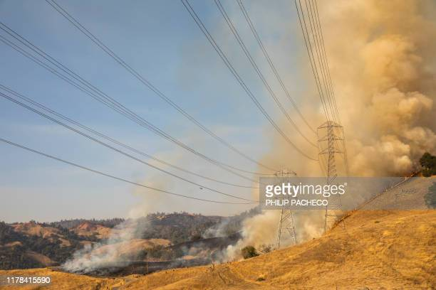 TOPSHOT A back fire set by fire fighters burns a hillside behind PGE power lines during firefighting operations to battle the Kincade Fire in...