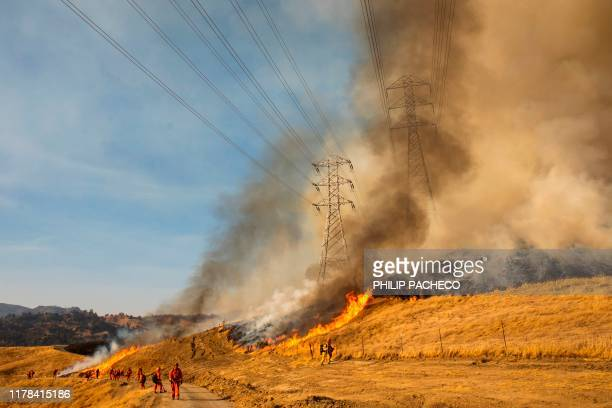 A back fire set by fire fighters burns a hillside near PGE power lines during firefighting operations to battle the Kincade Fire in Healdsburg...