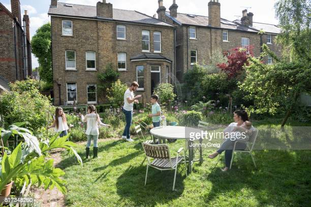 back garden and house with family spending time outdoors, mother with baby on chair - show garden stock photos and pictures