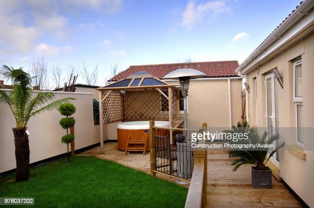 A back garden with a decking area and hot tub UK