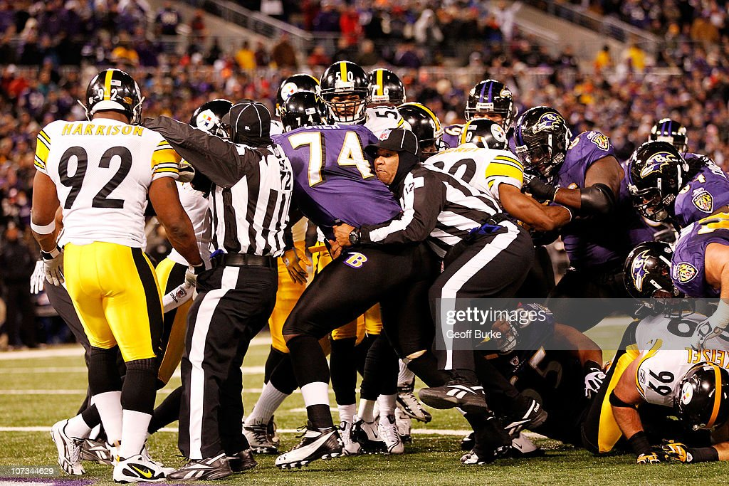 Back judge Greg Steed #12 and side judge Michael Banks #72 break up a scuffle between the Baltimore Ravens and the Pittsburgh Steelers during the first quarter of the game at M&T Bank Stadium on December 5, 2010 in Baltimore, Maryland.
