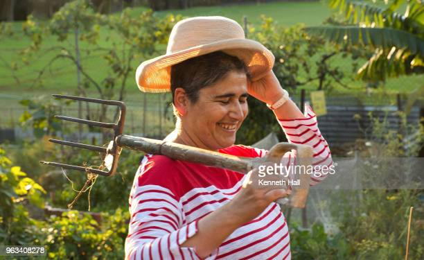 Back lighted model removing wide brimmed hat and carrying garden fork on right shoulder.