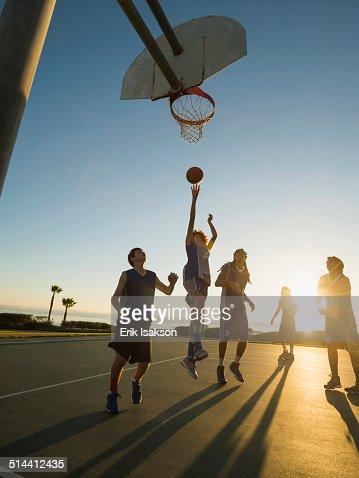 Back lit basketball teams playing on court