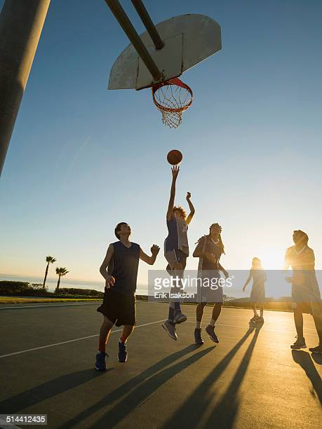Back lit basketball teams playing on court