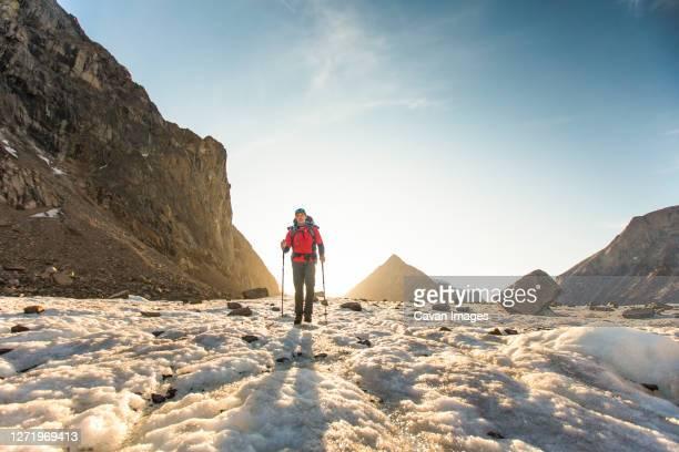 back lit mountaineer crosses glacier on baffin island. - バフィン島 ストックフォトと画像