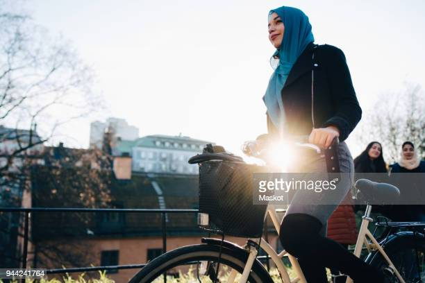 Back lit of young woman cycling by female friends against sky in city