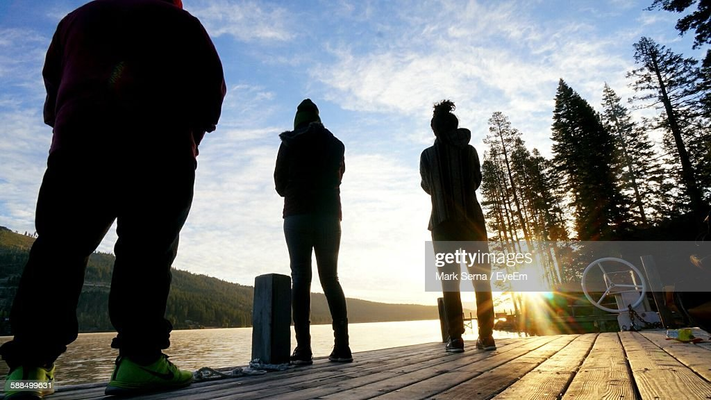 Lit A Donner back lit people standing on pier at donner lake against sky stock