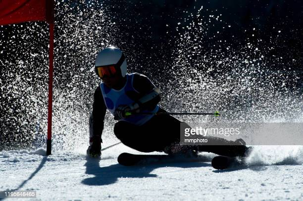 back lit shot of young adult alpine skier racing giant slalom - ski racing stock pictures, royalty-free photos & images