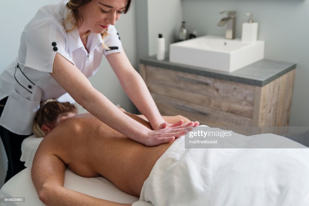 Back massage to mature woman in beauty spa. : Stock Photo