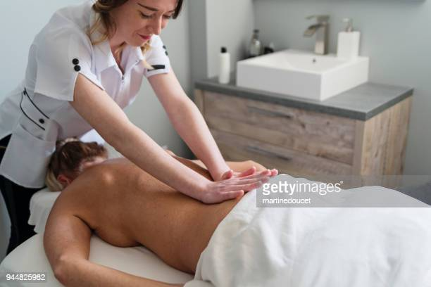 Back massage to mature woman in beauty spa.
