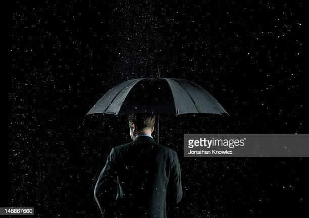 Back of a businessman under umbrella