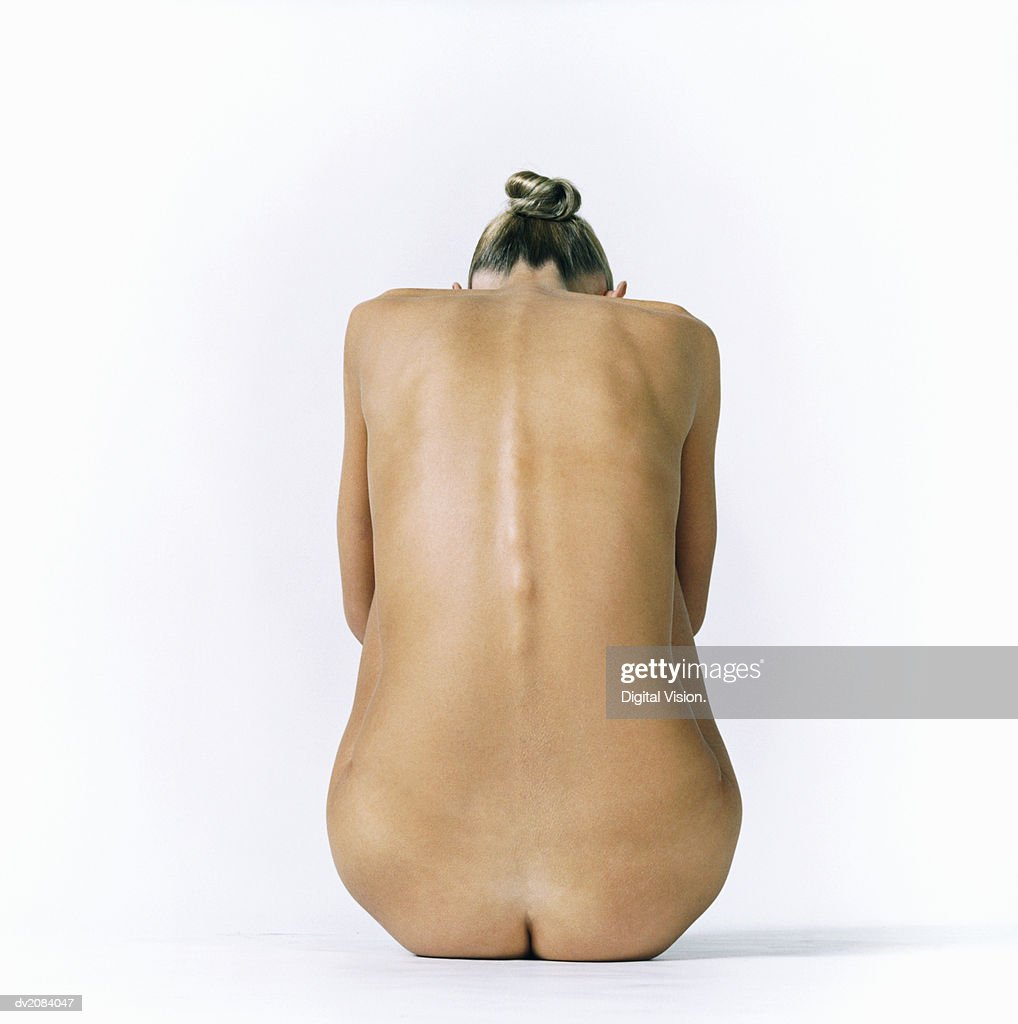 Back of a Naked Woman Sitting Down : Stock Photo