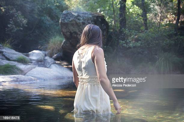 back of a young girl in a river in a white dress - waist deep in water stock pictures, royalty-free photos & images