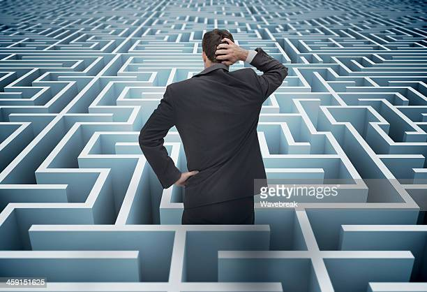 back of businessman getting lost in a maze - problemen stockfoto's en -beelden