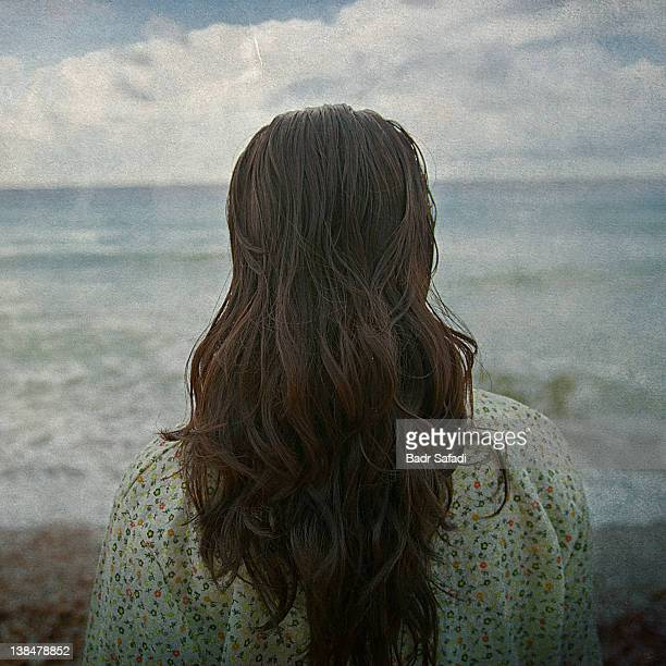 Back of head of woman standing looking at sea
