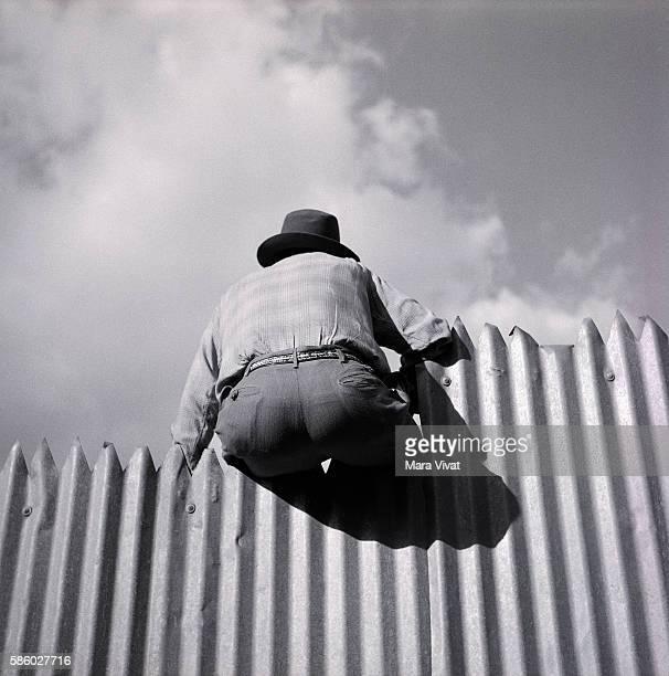 Back of Man Sitting on Corrugated Fence