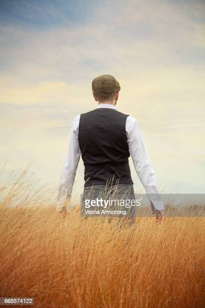 back of man standing in tall grass - waistcoat stock photos and pictures