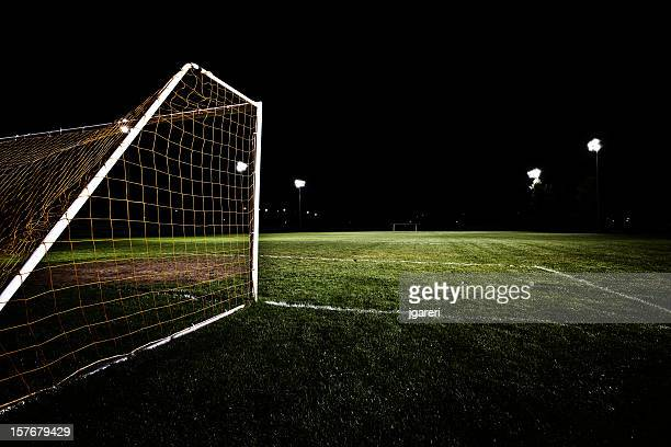 Back of soccer net on field in the middle of the night