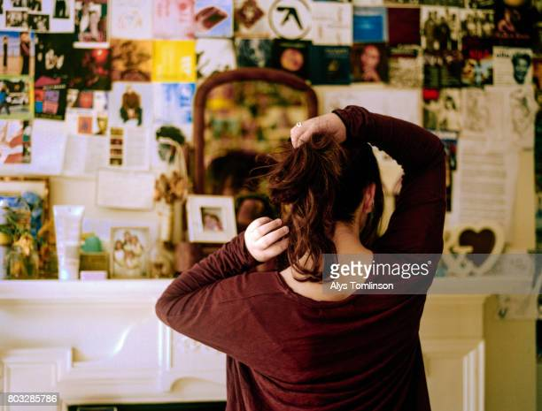back of teenage girl in bedroom, looking in mirror and doing her hair