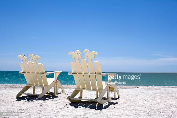 back of two white wooden chairs on sand with ocean - fort myers beach stock pictures, royalty-free photos & images