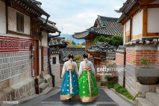 back of two woman wearing hanbok walking through the traditional style houses of bukchon hanok village in seoul, south korea. - south korea stock pictures, royalty-free photos & images