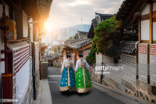 back of two woman wearing hanbok walking through the traditional style houses of bukchon hanok village in seoul, south korea. - korean culture stock pictures, royalty-free photos & images