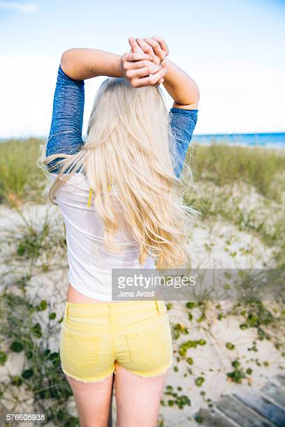 back of woman on beach - bleached hair stock photos and pictures