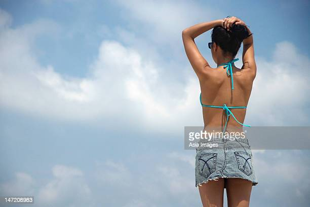 back of woman standing against sky - asian short skirt stock photos and pictures