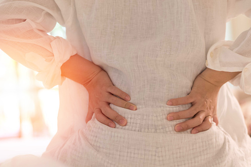 Back pain in woman concept. Female patient hurt from lower backache from bowel and bladder problems, palvic inflammatory disease (PID) or motherhood pregnancy. 1155320552