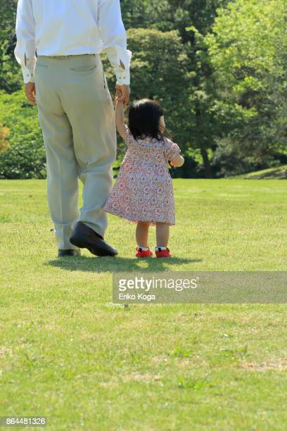 Back shot of granddaughter and grandfather walking hand in hand