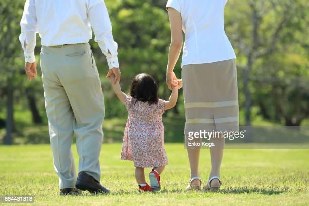 Back shot of granddaughter and grandparent walking hand in hand