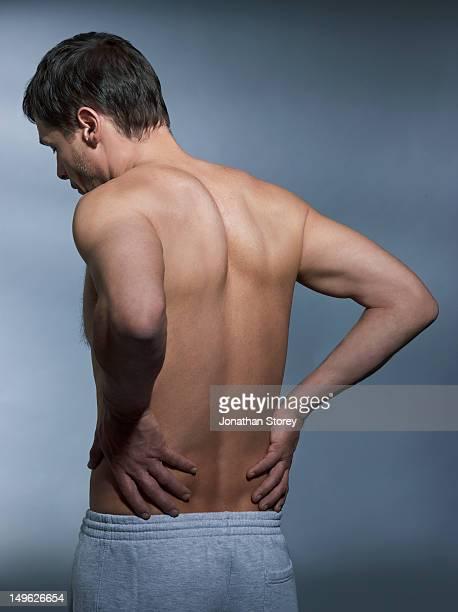 back shot of shirtless man, hands on lower back