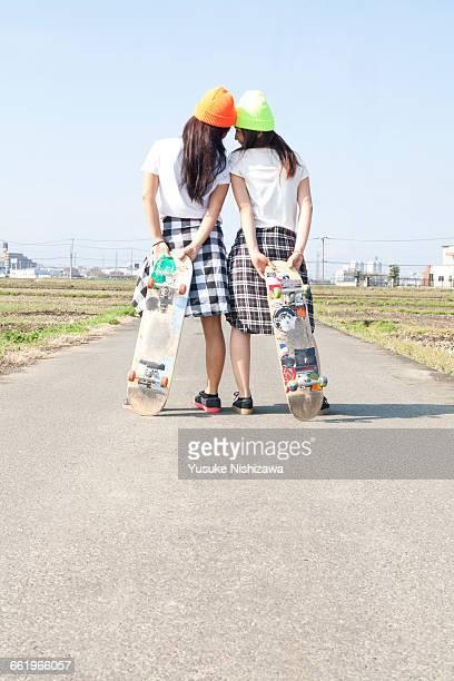 back shot of two girls skaters - yusuke nishizawa stockfoto's en -beelden