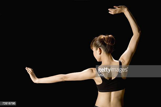 Back shot of woman performing martial arts, rear view, black background, copy space