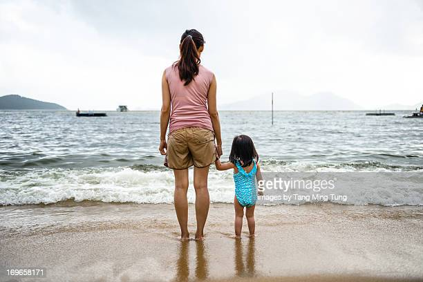 Back shot of young mom & toddler on the beach.