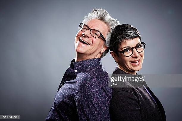 Back to back studio portrait of mature businessman and woman