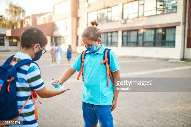 back to school - boys using hand sanitizer in schoolyard - doing a favor stock pictures, royalty-free photos & images