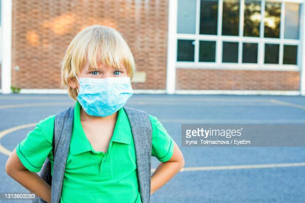 back to school concept after reopening. student at the schoolyard in face mask. - primary school child stock pictures, royalty-free photos & images
