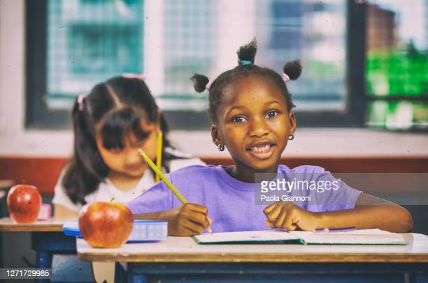 back to school. education concept. happy african elementary schoolgirl in class sitting at desk on first day of school - indigenous culture stock pictures, royalty-free photos & images