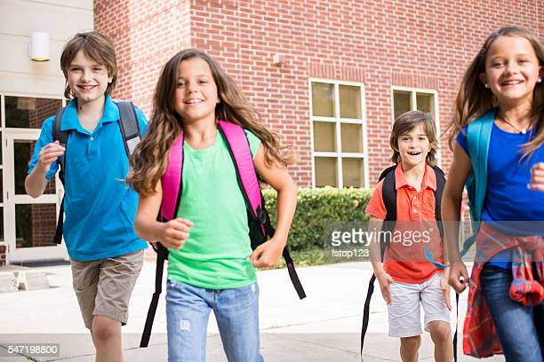 back to school:  elementary-age children, friends on school campus. - first day of summer stock pictures, royalty-free photos & images