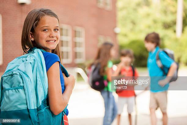 Back to School:  Elementary-age children, girl on school campus.