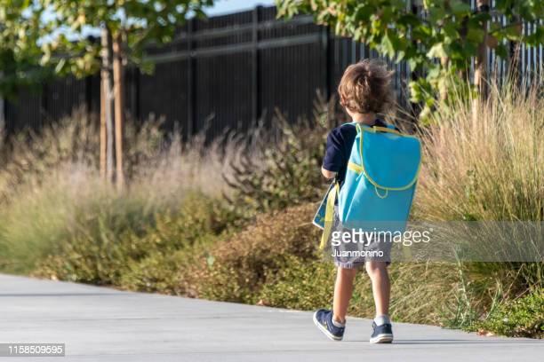 zurück zur schule, kleines junges kind zu fuß zu seinem ersten tag der schule - der erste schultag stock-fotos und bilder