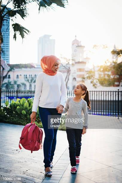 back to school - mother preparing daughter for school in asia - muslim mother stock pictures, royalty-free photos & images
