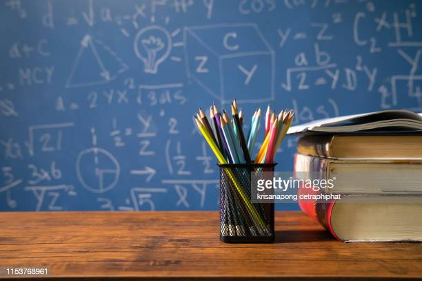 back to school supplies. books and blackboard on wooden background - teacher stock pictures, royalty-free photos & images